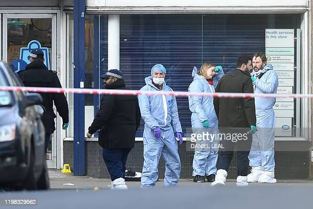 Police forensic officers work outside of a Boots store on Streatham High Road in south London on February 3 after a man was shot dead by police on...