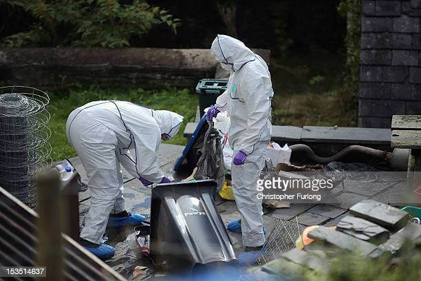 Police forensic scientists search rubbish bins outside the house of Mark Bridger in the village of Ceinws as the hunt for missing April Jones...