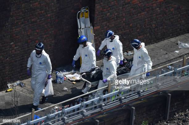 Police forensics carry a stretcher with a body bag on out of the 24 storey residential Grenfell Tower block in Latimer Road West London on June 14...