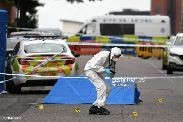 Police forensics officer gathers evidence near to forensics tents and evidence markers inside a cordon on Irving Street, following a major stabbing...