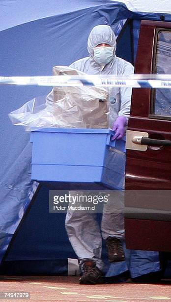 A police forensics officer removes evidence from a car suspected of carrying a bomb in Haymarket on June 29 2007 in London England The police were...