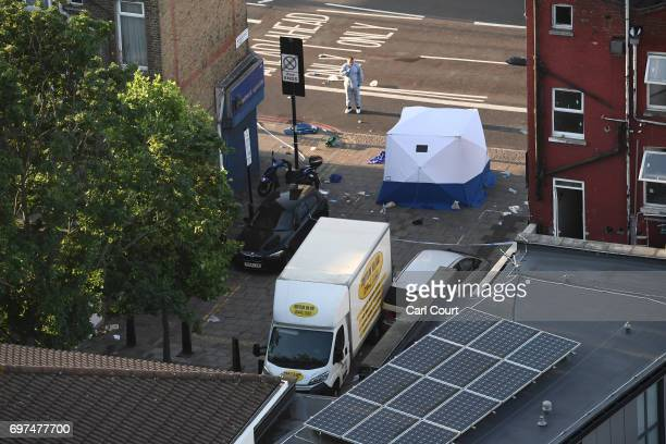 A police forensics officer stands next to a van believed to be involved in an incident near Finsbury Park Mosque in which the van ploughed into...
