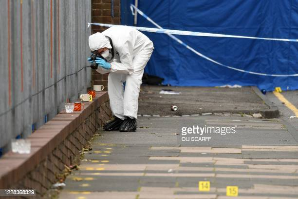 Police forensics officer takes photographs as he gathers evidence inside a cordon on Irving Street, following a major stabbing incident in the centre...