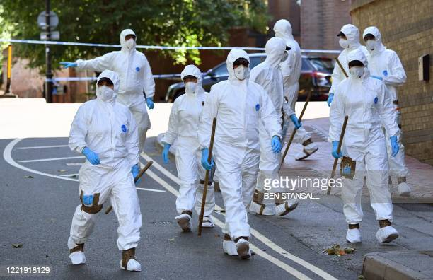 Police forensics officers dressed in Tyvek protective PPE suits and wearing masks, prepare to conduct a search as they work outside the walls of...