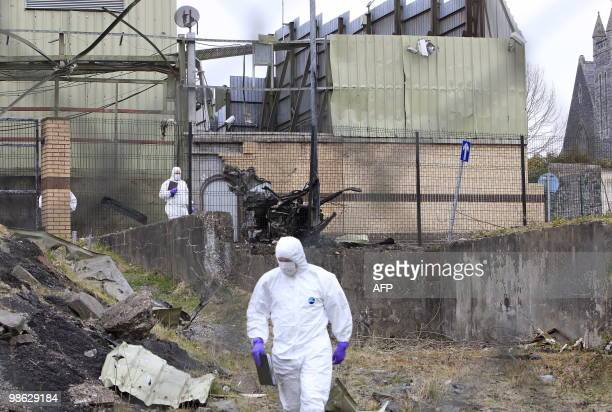 Police forensics officers inspect damage from a car bomb that exploded outside Newtownhamilton Police station in South Armagh Northern Ireland on...