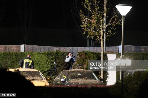 Police forensics officers search the area after an explosion damaged the bus of Borussia Dortmund some 10km away from the stadium prior to the UEFA...
