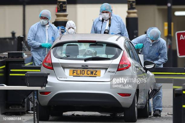 Police forensics officers work around a silver Ford Fiesta car that was driven into a barrier at the Houses of Parliament in central London on August...