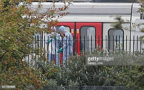 Police forensics officers works alongside an underground tube train at a platform at Parsons Green underground tube station in west London on...