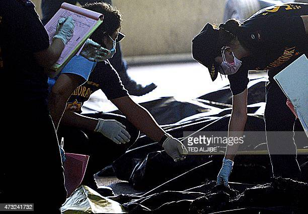 A police forensics team inspects the remains of victims inside body bags killed in a fire that gutted a footwear factory in Valenzuela City in...