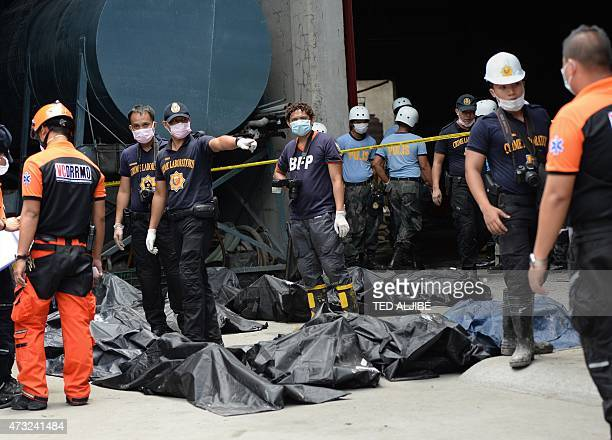 A police forensics team stands next to body bags containing the remains of victims killed in a fire that gutted a footwear factory in Valenzuela City...