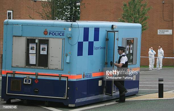 Police foresnsics officers work at the scene of a shooting which left one man dead and another injured last night in the Longsight area on July 28...