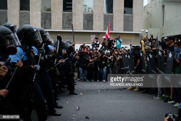 Police form a line in front of protesters during a May Day protest against pension cuts school closures and slow hurricane recovery efforts in San...