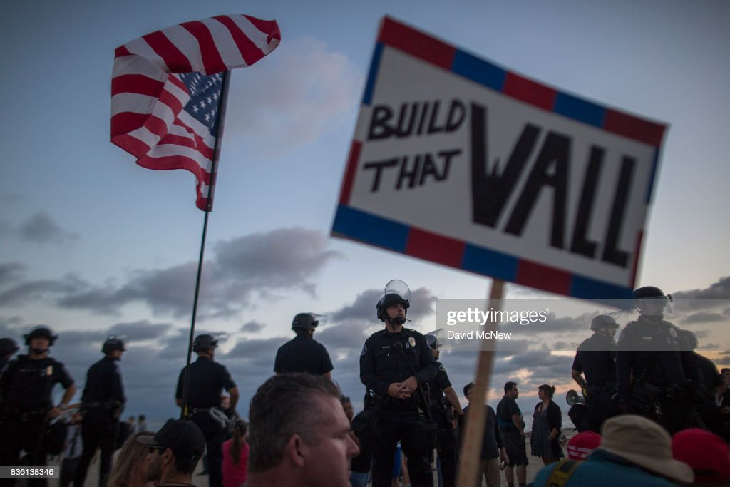 Police form a line on the boardwalk to keep demonstrators and counter demonstrators apart during an 'America First' demonstration on August 20, 2017 in Laguna Beach, California. Organizers of the rally describe it as a vigil for victims of illegal immigrants and refugees. Opponents say the demonstration is steeped in racism.