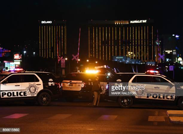 TOPSHOT Police form a perimeter around the road leading to the Mandalay Hotel after a gunman killed at least 50 people and wounded more than 200...