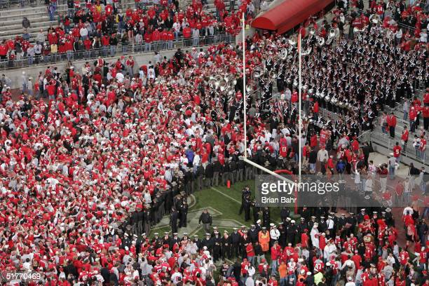Police form a wedge around the south end zone goalpost as Ohio State Buckeyes fans flood the field after upsetting the Michigan Wolverines on...