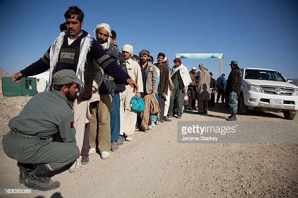 Police frisk Afghan labourers as they leave the site of a massive archeological dig in Logar Province, 35km south of Kabul, which has already yielded...