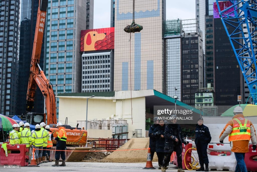 Police from the explosive ordinance disposal unit (R) chat as a defused US-made bomb (top), dropped during World War II, is lifted by crane above a harbourfront construction site a day after it was discovered in the Wan Chai district of Hong Kong on February 1, 2018. A wartime bomb was defused in Hong Kong on February 1 after a busy commercial district went into lockdown, with roads closed and thousands evacuated from surrounding shops, hotels and offices. / AFP PHOTO / Anthony WALLACE