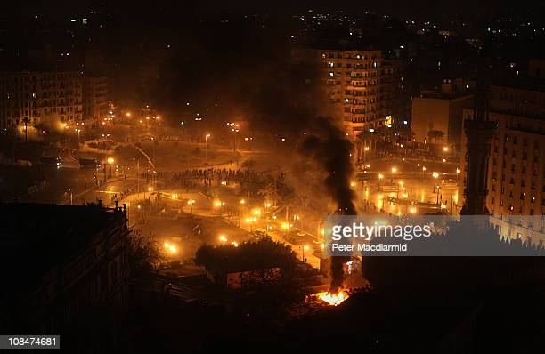 Police gather in Tahrir Square as a car burns on January 28, 2011 in Cairo, Egypt.Thousands of police are on the streets of the capital. Hundreds of...