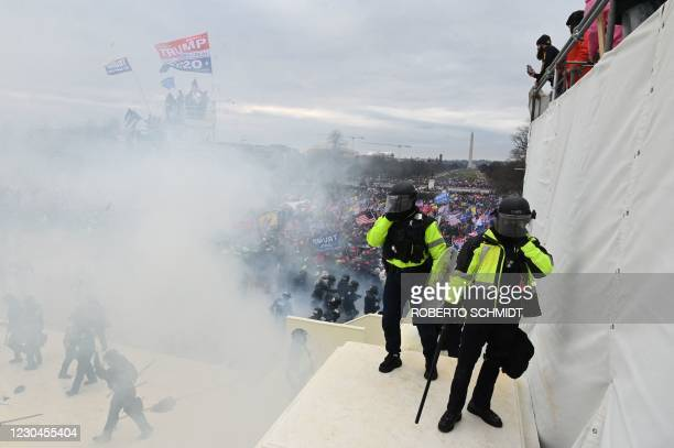 Police gather near tear gas as supporters of US President Donald Trump protest outside the US Capitol on January 6 in Washington, DC. - Demonstrators...