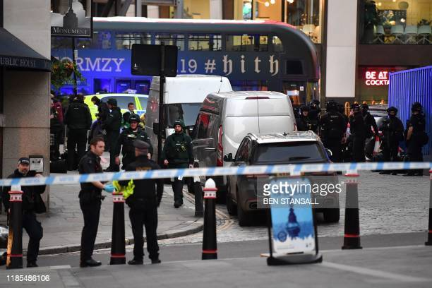 Police gather near The Monument in central London, on November 29 after reports of shots being fired on London Bridge. - Armed police shot a man on...