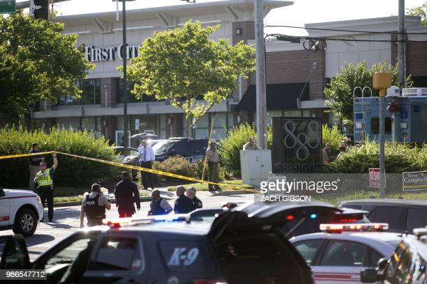 Police gather near the office of the Capital Gazette Newspaper in Annapolis Maryland on June 28 2018 At least five people were killed Thursday when a...