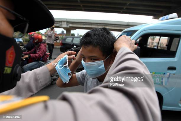 Police give masks on unused residents at a red light intersection, in Pangkalan Jati, Jakarta, on January 19,2021. The distribution of masks is...
