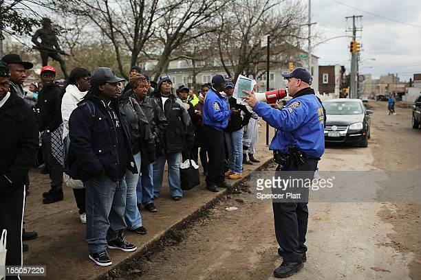 Police give residents emergency information in the Rockaway section of Queens after Hurricane Sandy on October 31, 2012 in the Queens borough of New...