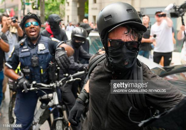 Police grab a member of an antifascist or Antifa group as they march while the AltRight movement gathers for a Demand Free Speech rally in Washington...