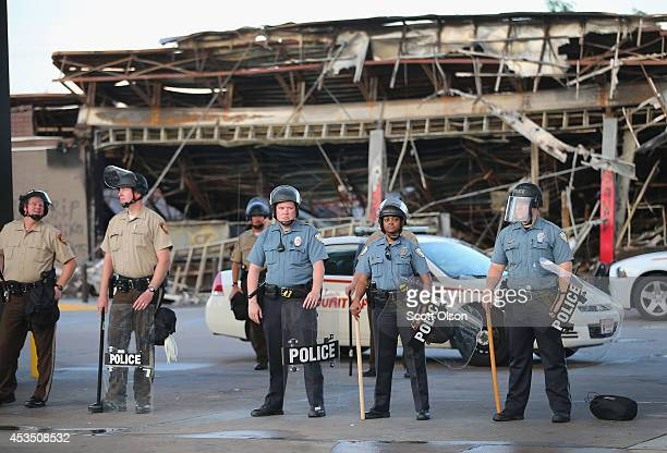 Police guard a Quick Trip gas station that was burned yesterday when protests over the killing of 18-year-old Michael Brown turned to riots and...