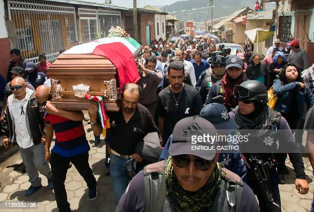 Police guard as relatives and friends of Nahuatzen Mayor David Otilica carry his coffin during his funeral in Nahuatzen Michoacan State Mexico on...