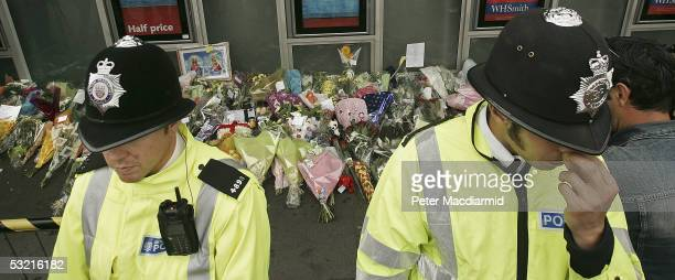 Police guard floral tributes at King's Cross railway station on July 9 2005 London At least 49 people were killed and 700 injured during morning rush...