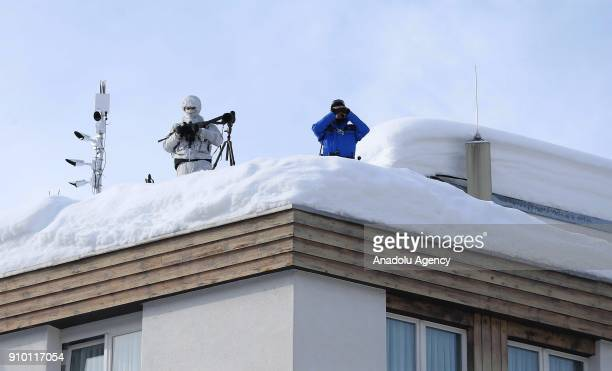 Police guard from a roof of a house as they take security measures while US President Donald J Trump is protested against countrywide during the 48th...