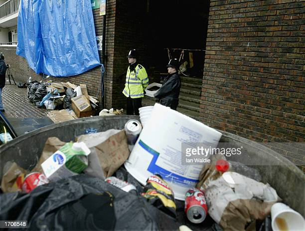Police guard the entrance to the apartment of a suspect wanted for questioning in connection with a double murder January 2 2003 in London Mutilated...