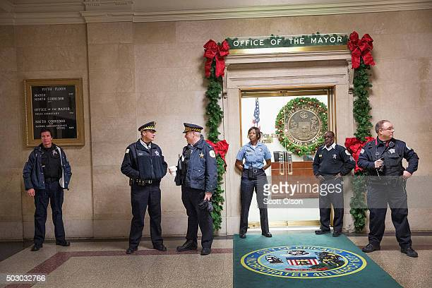 Police guard the entrance to the office of Mayor Rahm Emanuel as demonstrators calling for his resignation protest nearby on December 31 2015 in...