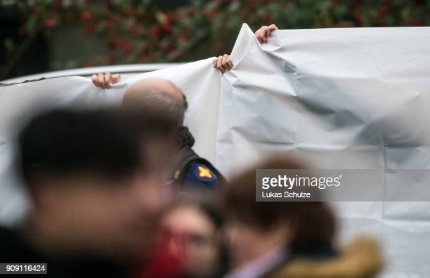 Police guards use tarpaulin to block the view as a body of a teenager is placed into a hearse at the Kaethe Kollwitz comprehensive school following...