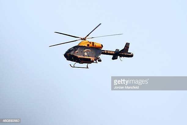 A police helicopter circles overhead at Gatwick airport in West Sussex on December 29 2014 in London England Flight VS43 was traveling to Las Vegas...