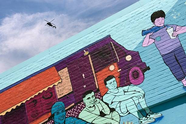 A Police Helicopter Circles The Neighborhood Over A Mural After An