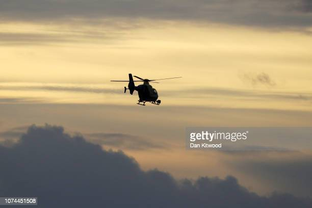 Police helicopter flies over Gatwick Airport as they search for the Drone operator causing closure of the airport on December 20 2018 in London...