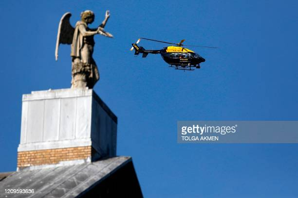 Police helicopter hovers over the people in Alexandra Park in north London on April 10, 2020 as warm weather tests the nationwide lockdown and the...