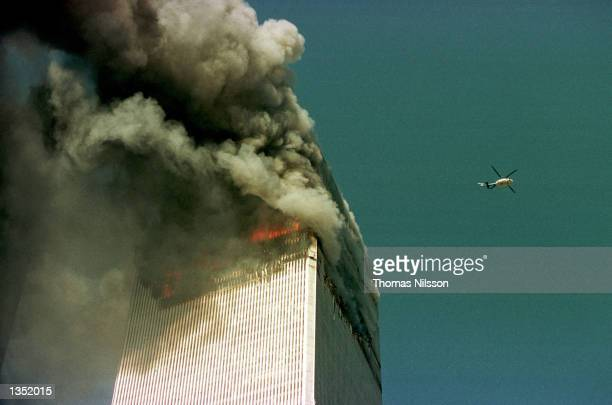 A police helicopter hovers over the World Trade Center's north tower September 11 2001 in New York City