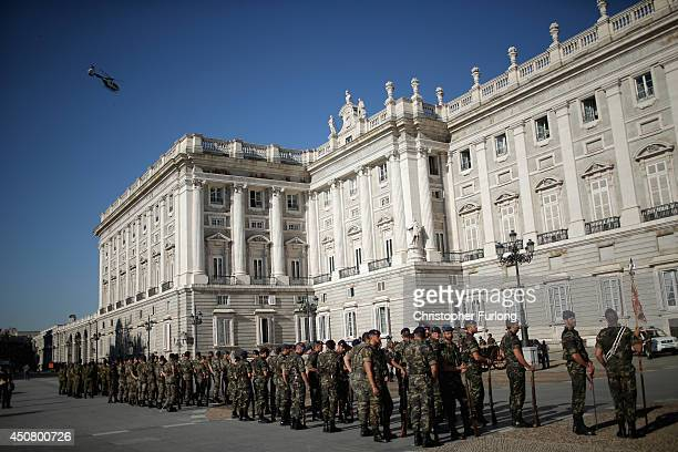 A police helicopter patrols over the Royal Palace as spanish soldiers rehearse their parade in preparation tomorrows coronation of Prince Felipe on...