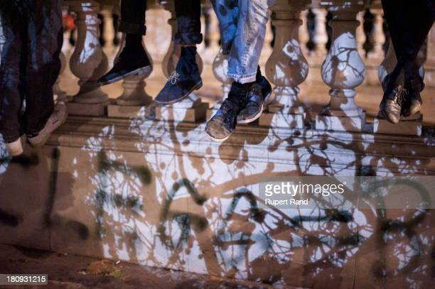 Police helicopter searchlight creates shadows of tree branches on the feet of protesters in Whitehall, London. The protests were against the rise in...