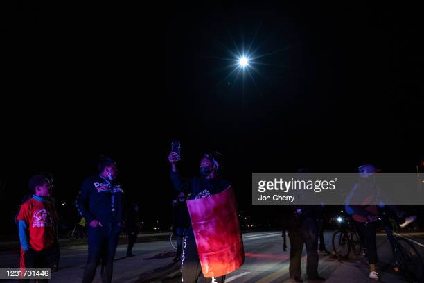 Police helicopter shines its light on protesters who accost police cars in front of them after the Breonna Taylor memorial events on March 13, 2021...