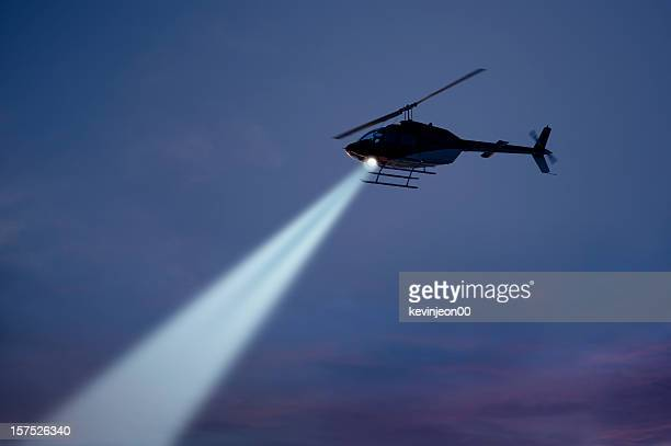 police helicopter shining a light beam in the dark sky - helicopter photos stock pictures, royalty-free photos & images