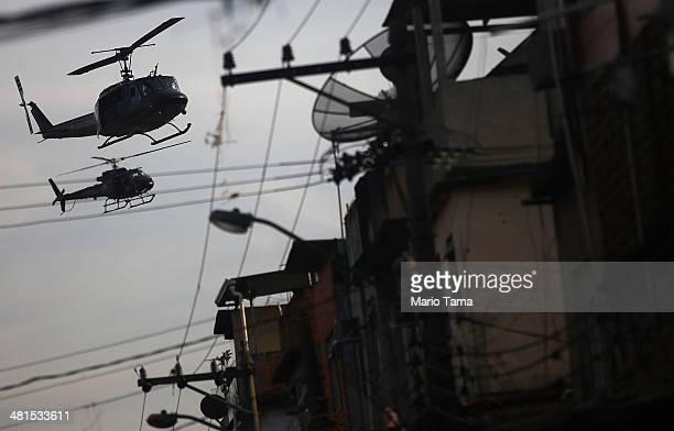 Police helicopters patrol the unpacified Complexo da Mare one of the largest 'favela' complexes in Rio on March 30 2014 in Rio de Janeiro Brazil The...
