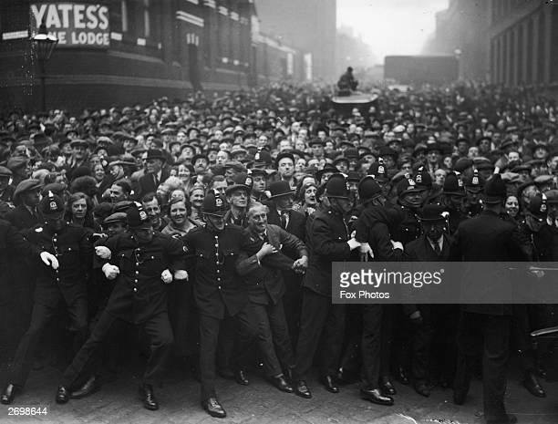Police hold back a crowd of sightseers outside Strangeways gaol in Manchester before the execution of Dr Buck Ruxton for the murder of his wife and...