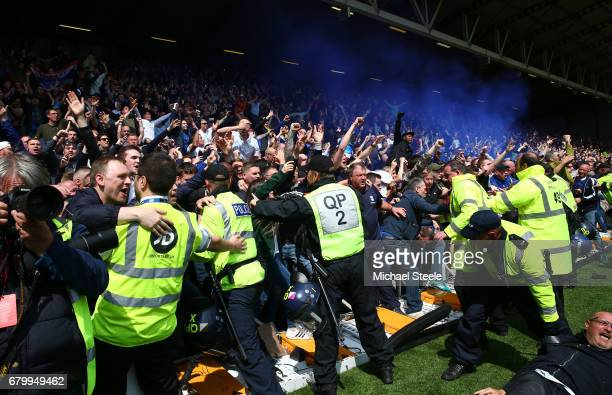 Police hold back Birmingham City fans back as they celebrate after their team avoid relegation after the Sky Bet Championship match between Bristol...