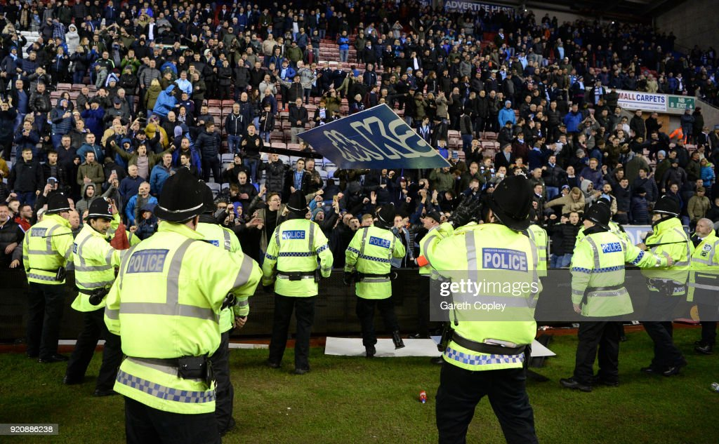Police hold back fans during a pitch invasion after the Emirates FA Cup Fifth Round match between Wigan Athletic and Manchester City at DW Stadium on February 19, 2018 in Wigan, England.