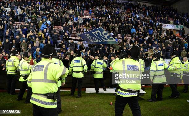 Police hold back fans during a pitch invasion after the Emirates FA Cup Fifth Round match between Wigan Athletic and Manchester City at DW Stadium on...