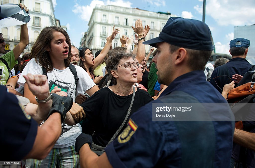 Police hold back protesters after an anti-evictions activist climber up a lampost as a protest against the Madrid 2020 Olympic Candidacy and Madrid County Council policy over evictions at Puerta del Sol on September 7, 2013 in Madrid, Spain.